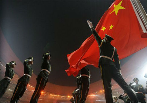Chinese soldiers salute the Chinese flag during the  2008 Olympic Games in Beijing / AP