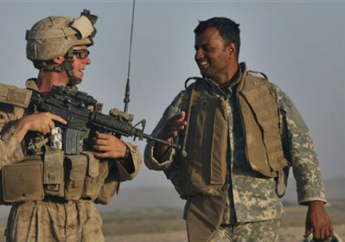 A U.S. Marine talks to an Afghan translator / AP