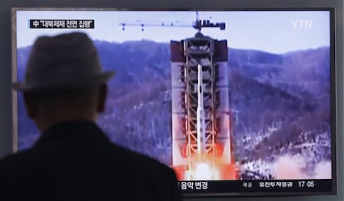 A man watches a TV news program showing a file footage of North Korea's rocket launch at Seoul Railway Station in Seoul
