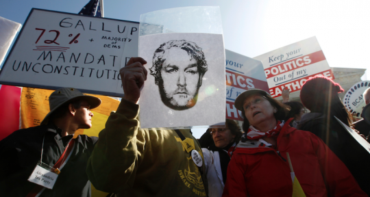 Andrew Breitbart fan holds drawing of the man outside Supreme Court rally shortly after his death / AP