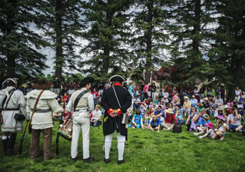 Revolutionary War re-enactors line up in front of a crowd / AP