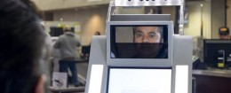 A man has his facial features and eyes scanned at a biometric kiosk