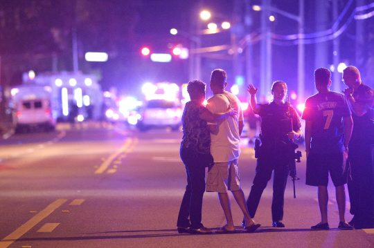 Orlando Police officers direct family members away from a fatal shooting at Pulse Orlando nightclub in Orlando, Fla., Sunday, June 12, 2016 / AP