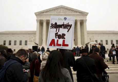 A demonstrator holds a sign aloft as the affirmative action in university admissions case was being heard at the Supreme Court in Washington