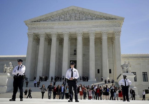 Immigration activists join hands after the U.S. Supreme Court heard arguments over the constitutionality of President Obama's executive action to defer deportation of certain immigrants, in Washington