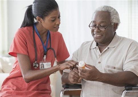 Caregiver explaining medications to older man in wheelchair / AP