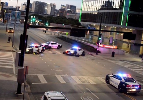 Police officers take cover behind their vehicles while under fire in downtown Dallas