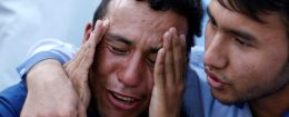 An Afghan man weeps outside a hospital after a suicide attack in Kabul, Afghanistan