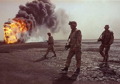 A U.S. Marine patrol walks across the charred oil landscape near a burning well during perimeter security patrol near Kuwait City in 1991