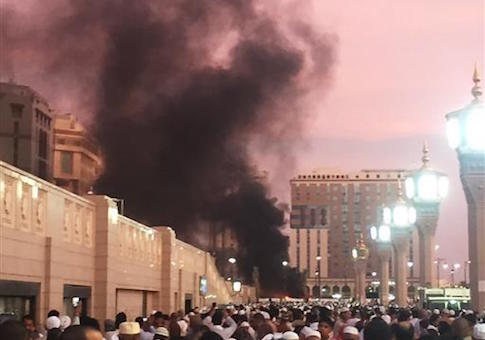 People stand by an explosion site in Medina, Saudi Arabia