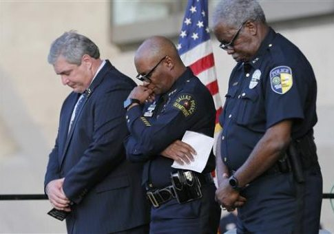 Dallas police chief David Brown, center, takes part in a candle light vigil at City Hall, Monday, July 11, 2016, in Dallas / AP