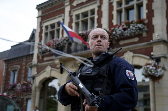 A policeman in front of the city hall after two assailants had taken five people hostage in the church at Saint-Etienne-du -Rouvray near Rouen in Normandy, France, July 26, 2016 / REUTERS