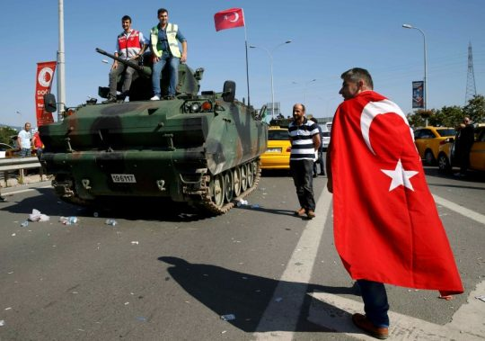 A man wrapped in a Turkish flag walks past a military vehicle in front of Sabiha Airport, in Istanbul, Turkey July 16, 2016. REUTERS / Baz Ratner