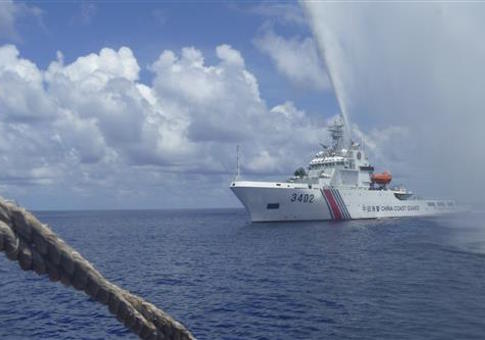 Chinese Coast Guard members approach Filipino fishermen off Scarborough Shoal / AP