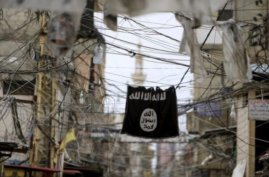 An ISIS flag hangs amid electric wires over a street in Ain al-Hilweh Palestinian refugee camp, near the port-city of Sidon, southern Lebanon January 19, 2016 / REUTERS