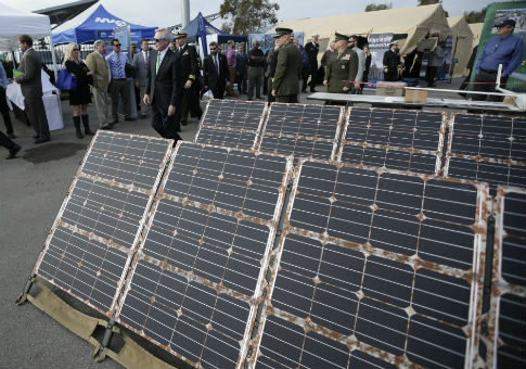 Navy Secretary Ray Mabus, behind, walks past banks of solar power harnessing devices / AP