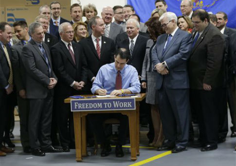 Republican Gov. Scott Walker signs Wisconsin's right-to-work law / AP