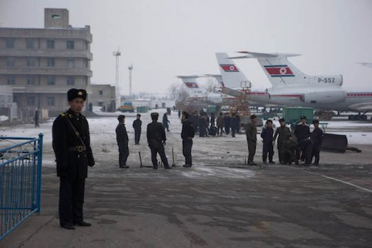 North Korean workers labor next to Air Koryo jets lined up on the tarmac of the airport near Pyongyang, North Korea / AP