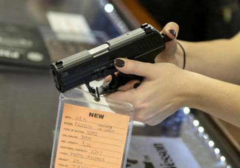 A gun store customer examines a handgun / AP