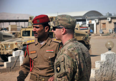 A U.S. Army soldier speaks to his Iraqi army counterpart at Camp Swift, Iraq / AP