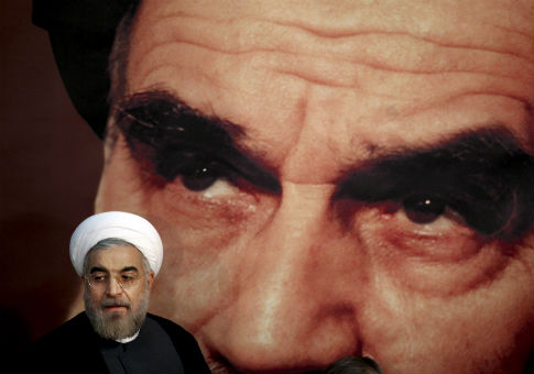 Hassan Rouhani in front of a portrait of Iranian revolutionary founder Ayatollah Khomeini / AP