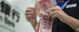 A Chinese clerk counts RMB (renminbi) yuan banknotes at a branch of China Construction Bank