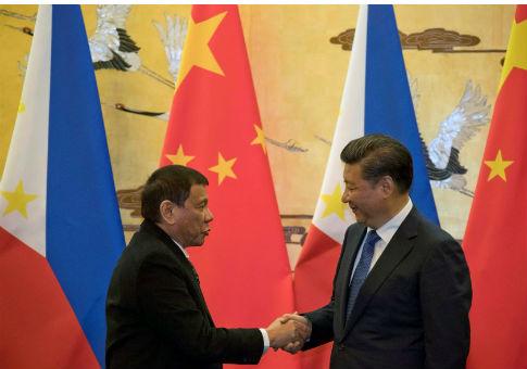 Philippine President Rodrigo Duterte (L) and Chinese President Xi Jinping shake hands / REUTERS