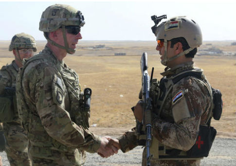 U.S. Army Maj. Gen. Gary J. Volesky, left, commander, Combined Joint Forces Land Component Command – Operation Inherent Resolve, visiting with an Iraqi soldier / AP