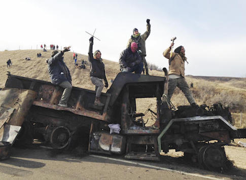 Protesters against the Dakota Access oil pipeline stand on a burned-out truck / AP