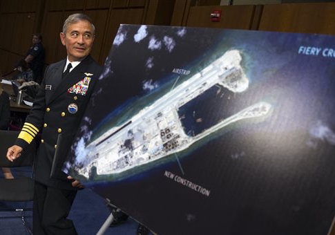 Adm. Harry Harris walks past a photograph of Chinese island-building in the South China Sea / AP