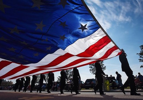 An oversized American Flag is carried during the start of a Veterans Day Parade