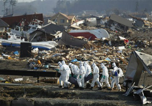Japanese police officers carry a body in the area devastated by the March 11, 2011 earthquake near the tsunami-crippled Fukushima Dai-ichi nuclear power plant / AP
