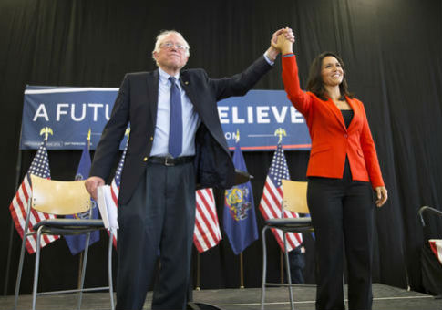 Sen. Bernie Sanders (I., Vt.) holds hands with Rep. Tulsi Gabbard (D., Hawaii) / AP