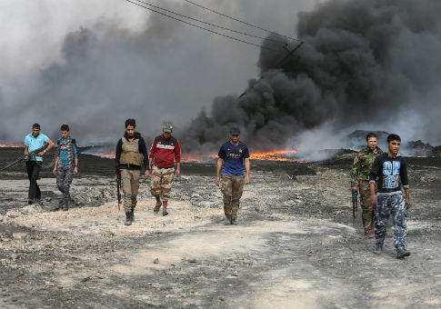 Tribal fighters walk as fire and smoke rises from oil wells, set ablaze by ISIS in Qayyara, Iraq / REUTERS