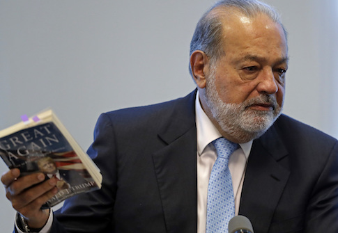 Mexican billionaire Carlos Slim holding a book by U.S. President Donald Trump / AP