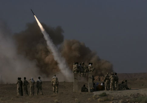Members of Iran's revolutionary guard look at surface to surface missile launched during war game, June 28, 2011 / REUTERS