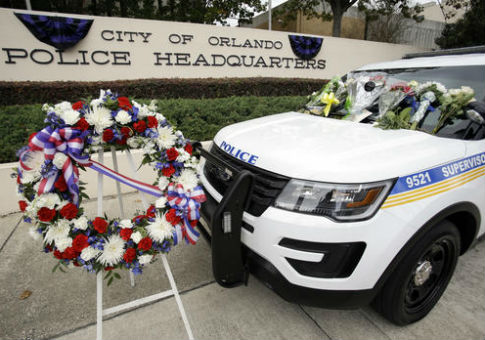 Wreath and flowers surround Orlando police shooting victim, officer Debra Clayton's patrol car, in front of police headquarters / AP