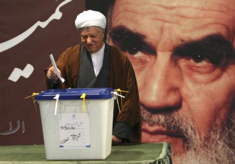 Former Iranian President Akbar Hashemi Rafsanjani, with a poster of Ayatollah Ruhollah Khomeini / REUTERS