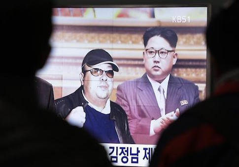 A TV screen shows pictures of North Korean leader Kim Jong Un and his older brother Kim Jong Nam