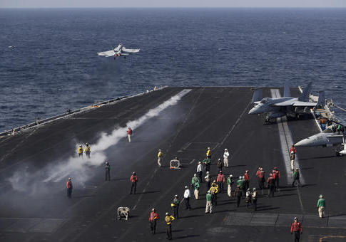 A U.S. Navy fighter jet takes off from the deck of the U.S.S. Dwight D. Eisenhower aircraft carrier
