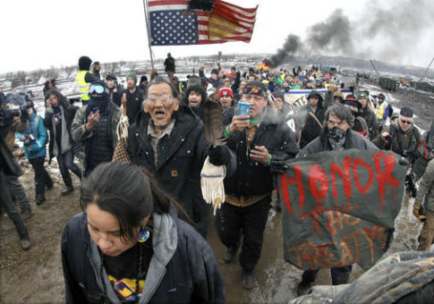 Large crowd representing majority of remaining Dakota Access Pipeline protesters march out of Oceti Sakowin camp / AP