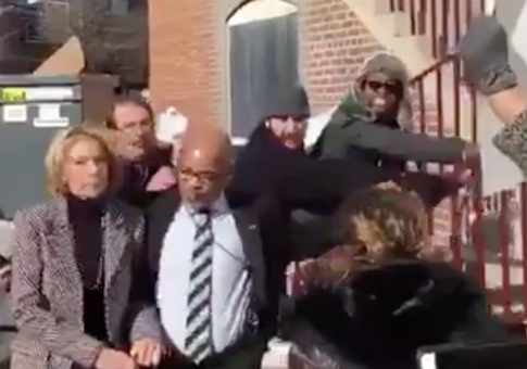 Sec. of Education Betsy DeVos, left, escorted away from protesters / Twitter video screenshot