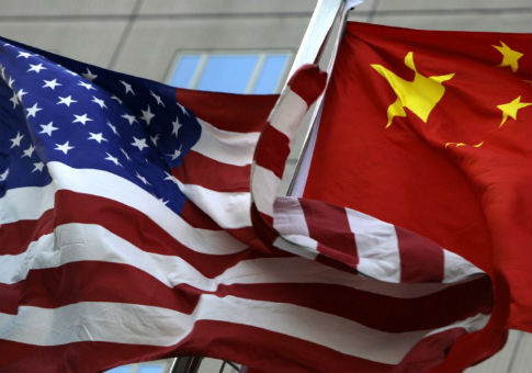 National flags of U.S. and China wave in front of an international hotel in Beijing / REUTERS