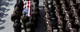 Members of law enforcement community salute as St. Louis County police officer Blake Snyder's casket is carried out of his funeral service / AP