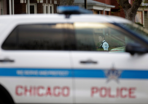 A Chicago Police officer is seen through a police vehicle window