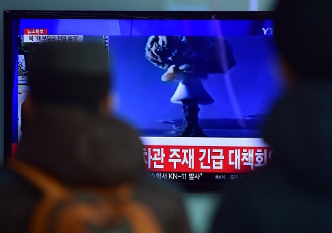 People watch a news report on North Korea's first H-bomb test at a railroad station in Seoul on January 6 / Getty Images