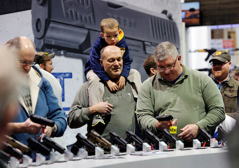 Visitors view a gun display at a National Rifle Association outdoor sports trade