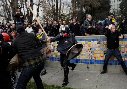 """A demonstrator in support of U.S. President Donald Trump swings a stick towards a group of counter-protesters during a """"People 4 Trump"""" rally in Berkeley, California"""