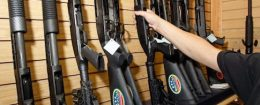 A sales associate takes a gun from a display of shotguns at The Gun Store in Las Vegas