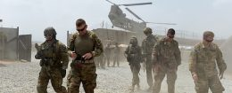 US army soldiers walk as a NATO helicopter flies overhead at coalition force Forward Operating Base (FOB) Connelly in the Khogyani district in the eastern province of Nangarhar